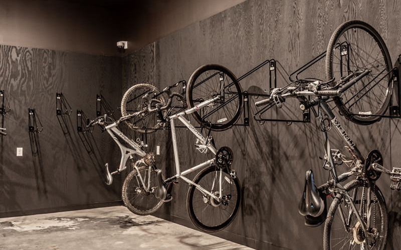 concrete floored bicycle storage room with bikes hanging on wall mounts