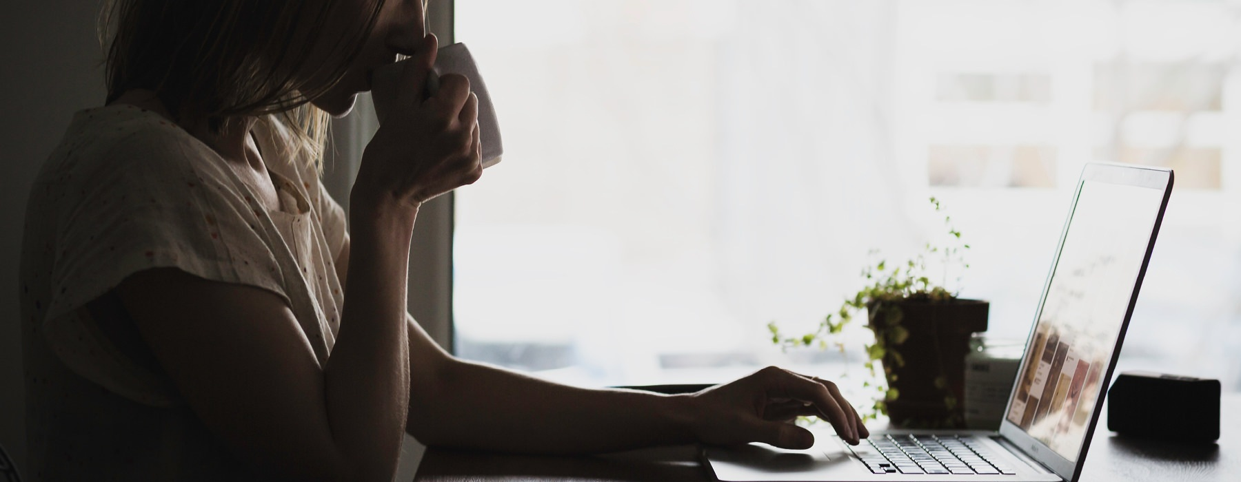 partially silhouetted woman sips coffee as she works, at her laptop, in front of large, bright window