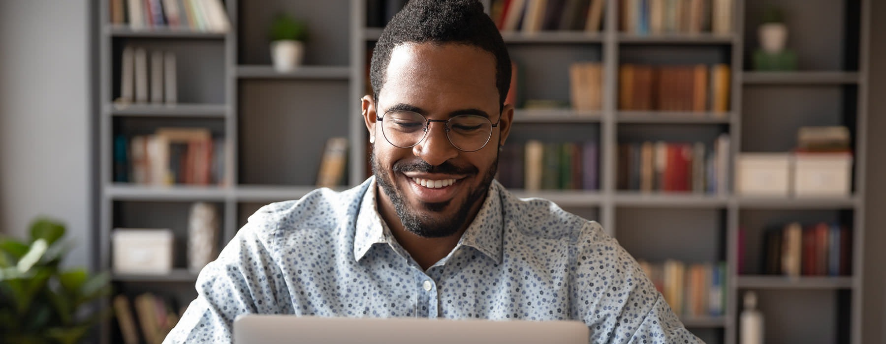 happy, young man works on his laptop in a room with bookshelves and plants